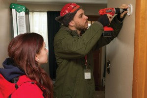 An American Red Cross volunteer helps install a smoke alarm.
